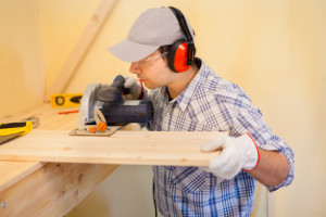 Carpenter using a circular saw to cut a wood board